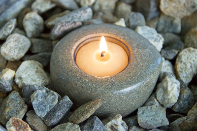 Hand-carved riverstone tea light made in Haiti by artisans with 100% pure beeswax tea lights.