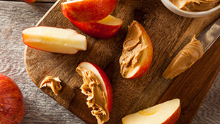 Peanut butter spread on a delicious red apple
