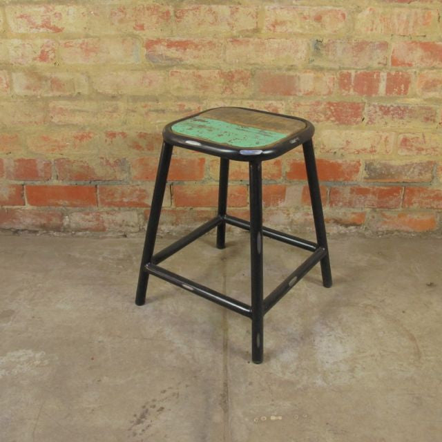 Industrial style stool with short legs and a timber seat