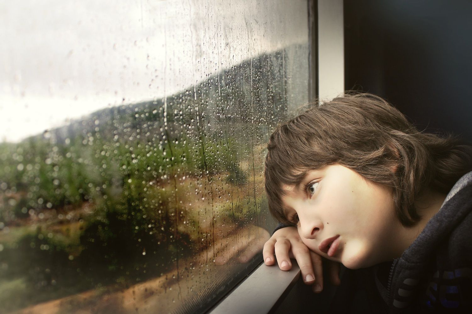 Depressed Boy Staring Out of a Window - How to Identify Children Suffering from ACEs