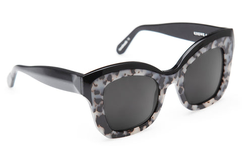 Beveled temples, flat lenses, and a square silhouette make Dauphine the ultimate oversized statement frame.  Free shipping and lifetime warranty. Features grey flat lens and handcrafted black acetate frame.
