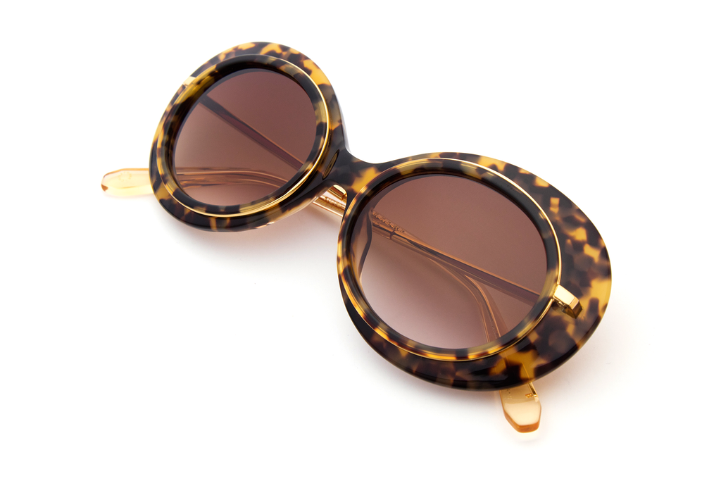 Named for the all-female Mardi Gras krewe, Iris features hand-carved acetate united with a custom metal rim wire. Its oblong shape makes for a bold statement frame.  As seen on Gigi Hadid. Free shipping and lifetime warranty.  Features amber gradient lens and handcrafted blonde tortoise acetate frame with 24K plated gold hardware.