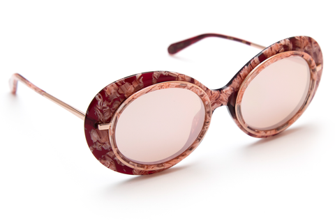 Named for the all-female Mardi Gras krewe, Iris features hand-carved acetate united with a custom metal rim wire. Its oblong shape makes for a bold statement frame.  As seen on Gigi Hadid. Free shipping and lifetime warranty.  Features rose mirrored lens and handcrafted calypso rose gold acetate frame with 24K plated gold hardware.