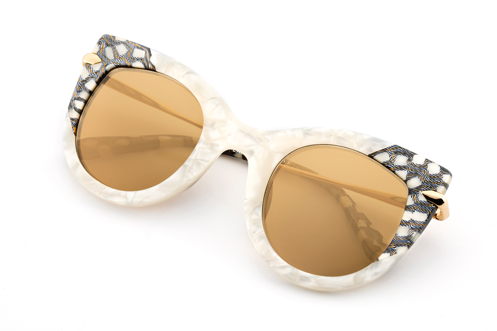 Named for the infamous Voodoo queen, Laveau's confident, upswept cat-eye silhouette merges both metal and acetate with a flattering yet enchanting allure.  Free shipping / free returns and lifetime warranty.  Gold mirrored lens and a handcrafted Stella custom acetate frame with 24K gold plated hardware.