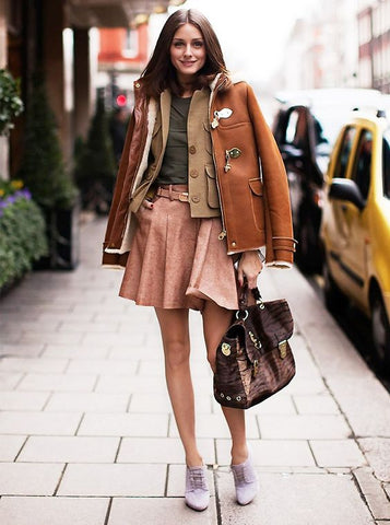 Olivia Palermo wearing a camel coat over a belted beige skirt