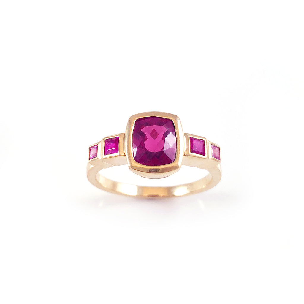 Royalty ring with a Dark Pink Spinel in between Rubies and Sapphires in 9 carat Yellow Gold