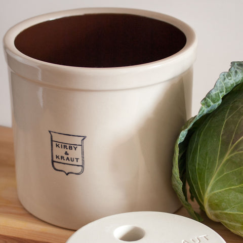Stoneware fermentation crock with weight.