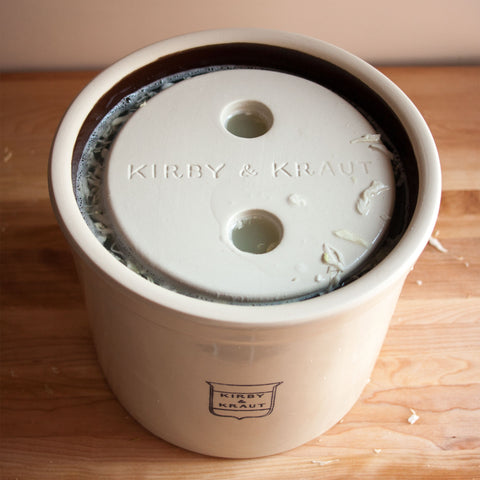 Stoneware weight on a batch of sauerkraut in a crock.