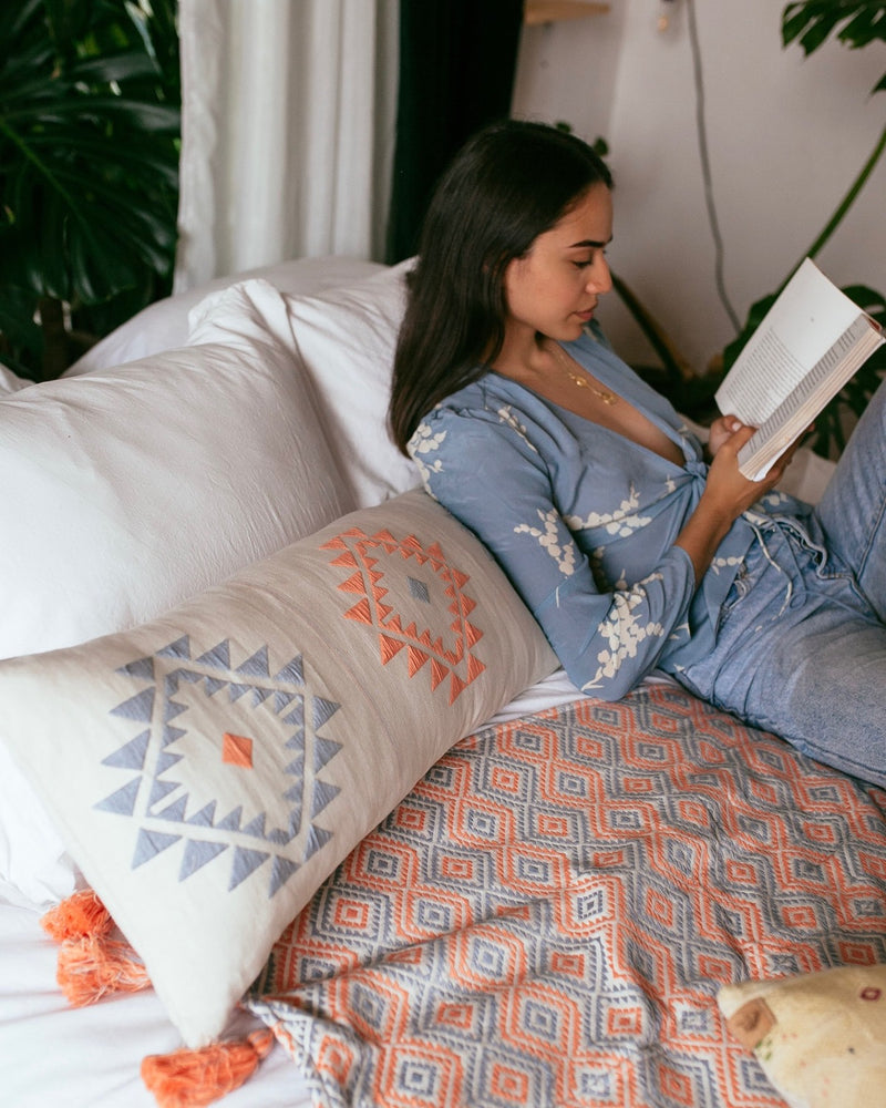 Model reading in bed against a Chile Verde Lumbar Cushion from Story of Source