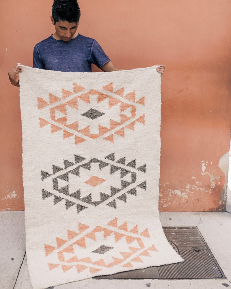 Artisan showing off the Story of Source Chile Verde Rug he wove