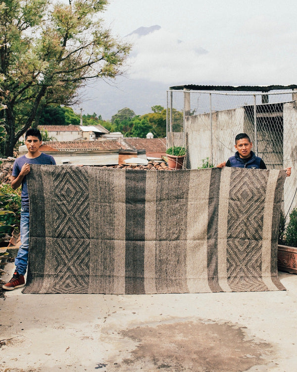 Jun Batz Artisans Showing off the Story of Source Striped Pepenado Rug
