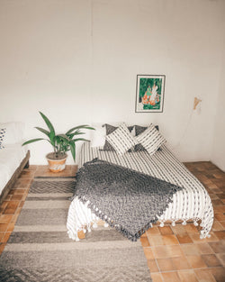Story of Source Striped Pepenado Rug styled in a bedroom