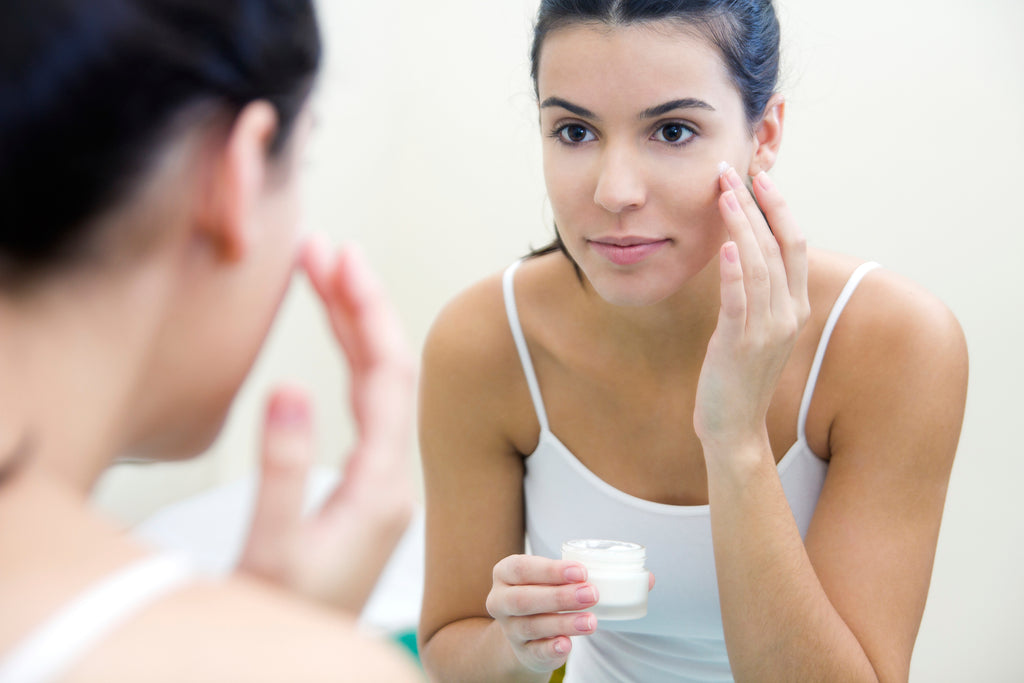 Woman applying skincare products to her skin