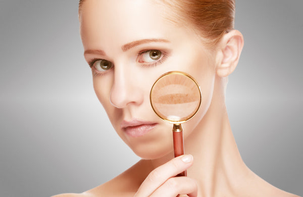 Woman with a beautiful complexion holding a magnifying glass to her skin