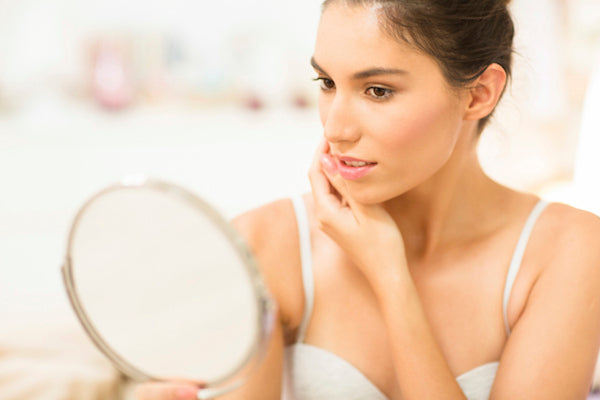 woman with mirror looking at acne skincare concerns