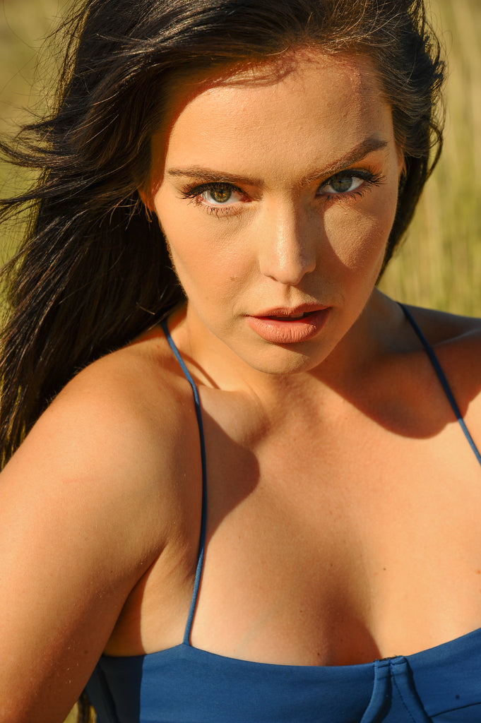 Model in blue swimsuit staring intensively into camera