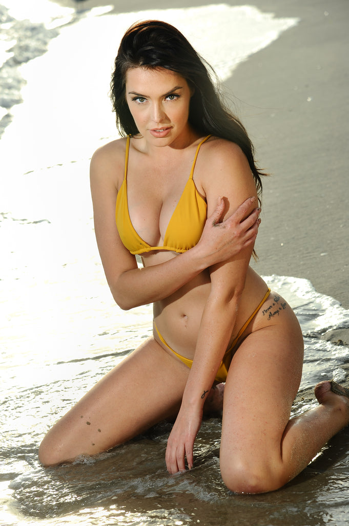 Model wearing gold swimsuit while sitting on the beach in the rays of setting sun