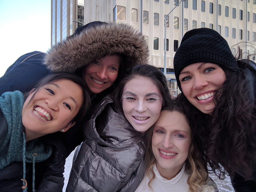 Five women huddled together in the cold, smiling for a group selfie