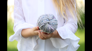 girl in white shirt holds skein of handspun yarn