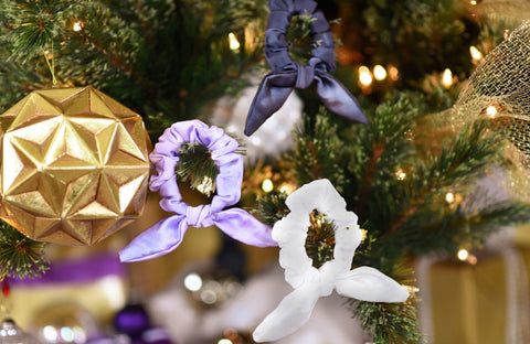 Three silk scrunchies hang as ornaments on a Christmas tree