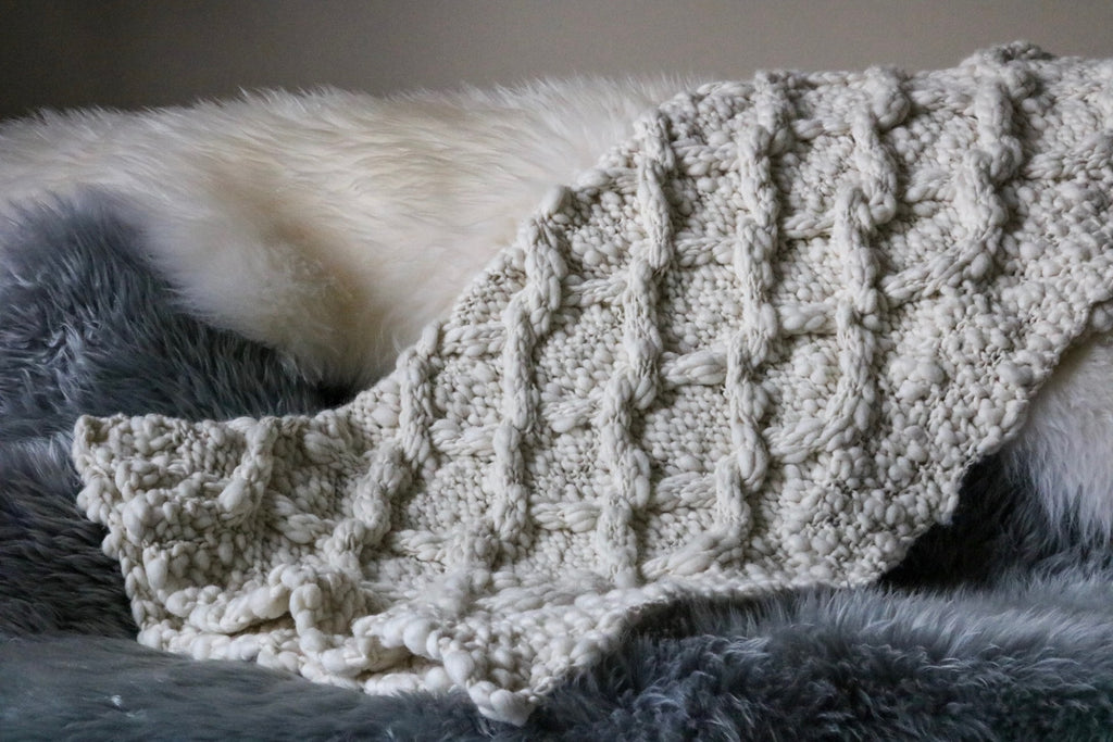 White wool throw blanket lays draped across grey and white wool fleece