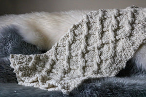 A textured cable knit blanket lays across a fleecy couch
