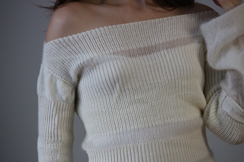 closeup shot of model wearing kid mohair silk and wool cream sweater off the shoulder