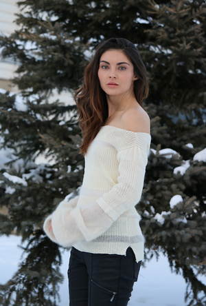 Model standing in snow beside spruce tree wearing soft white merino wool and kid mohair sweater