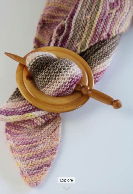 round apple wood shawl fastener holds pink and brown shawl with Amur cherry pin