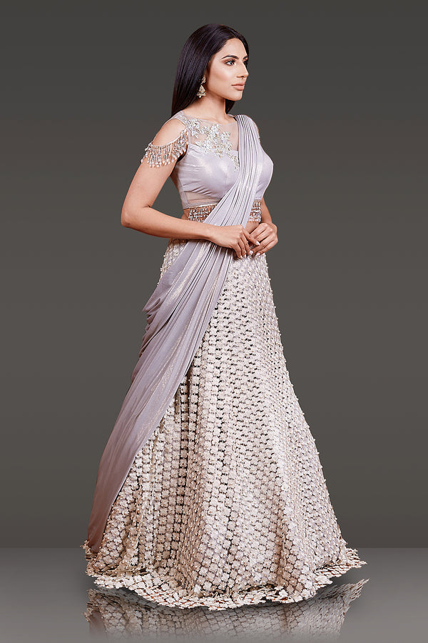 LIGHT GREY STITCHED LYCRA DUPATTA WITH SHRINES TOP HAND EMBROIDERY ON THE OPPOSITE SHOULDER PAIRED WITH A FLORAL LASER CUT SKIRT,TASSELS ON THE BLOUSE