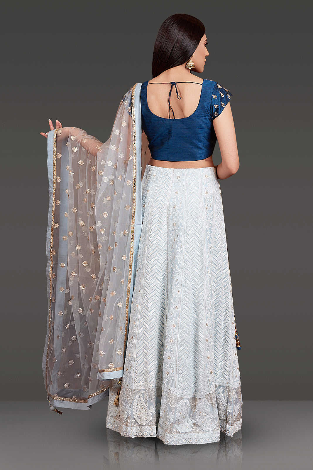 MIDNIGHT BLUE RAW SILK TOP WITH STONE & PEARL EMBROIDERY PAIRED WITH SKY BLUE CHICKANKARI HIGHLIGHTED SKIRT AND NET DUPATTA