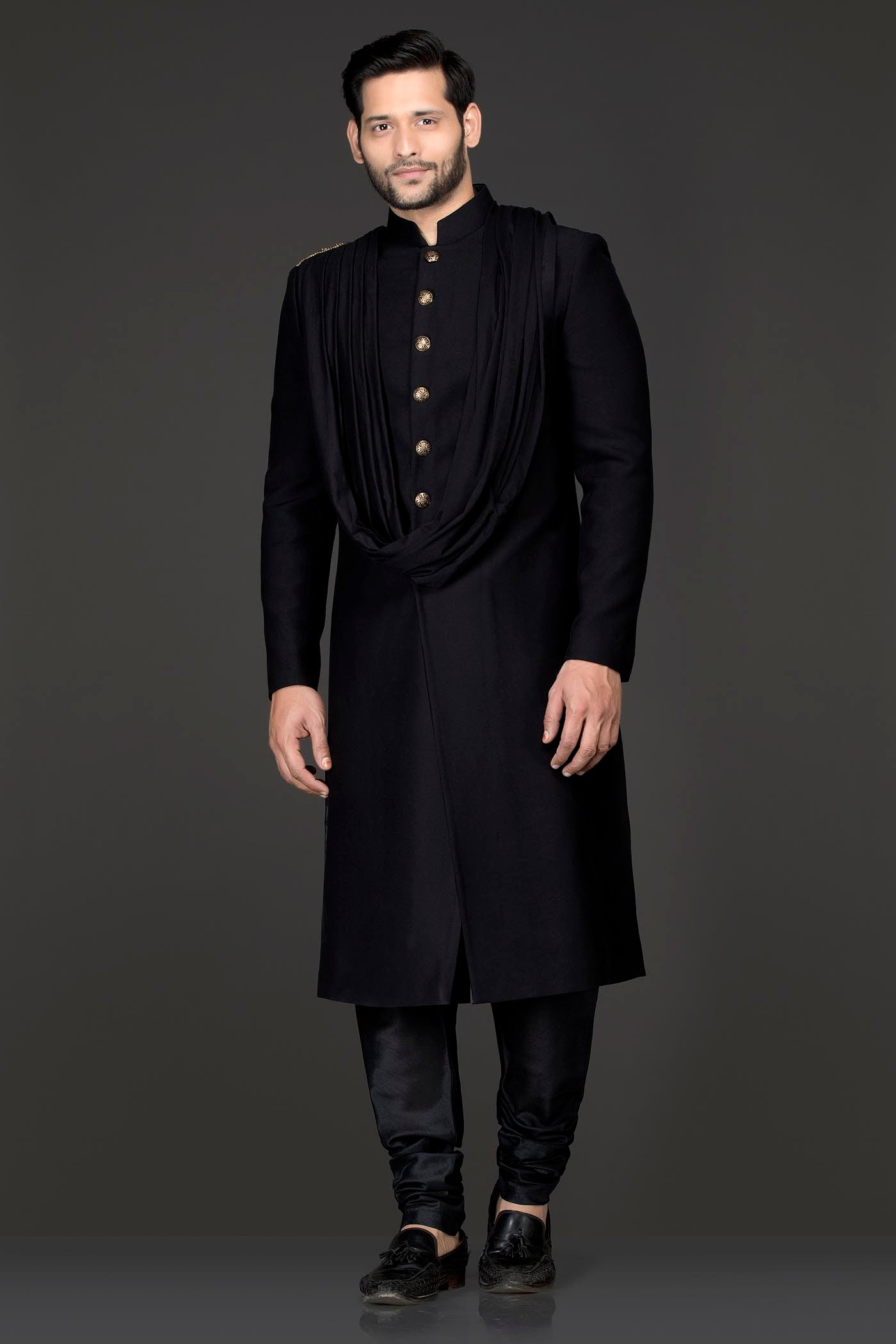 Black Colour Suiting Fabric Long Jacket With Attached Shoulder Lycra Drape And A Gold Tassel Brooch On The Shoulder Paired With Black Chudidar