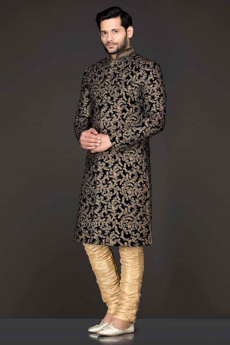 Navy Blue Velvet Sherwani Covered With Gold Zari Embroidery Paired With Gold Chudidar
