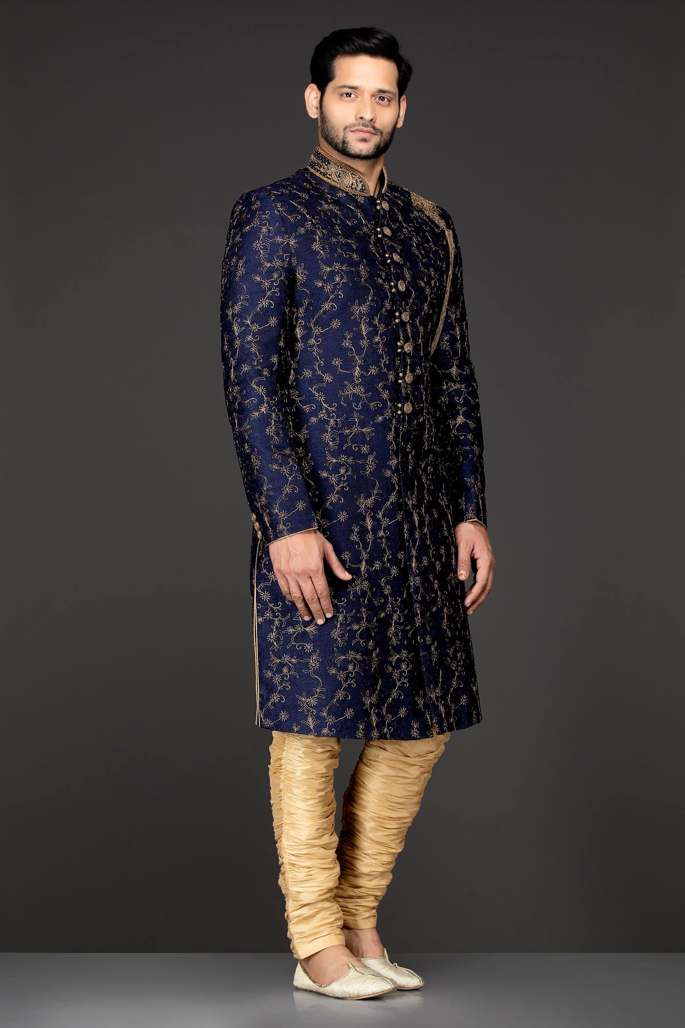 Navy Blue Silk Sherwani With Embroidery On The Collar And Shoulder Brooch With Hanging Tassels Paired With Gold Trousers