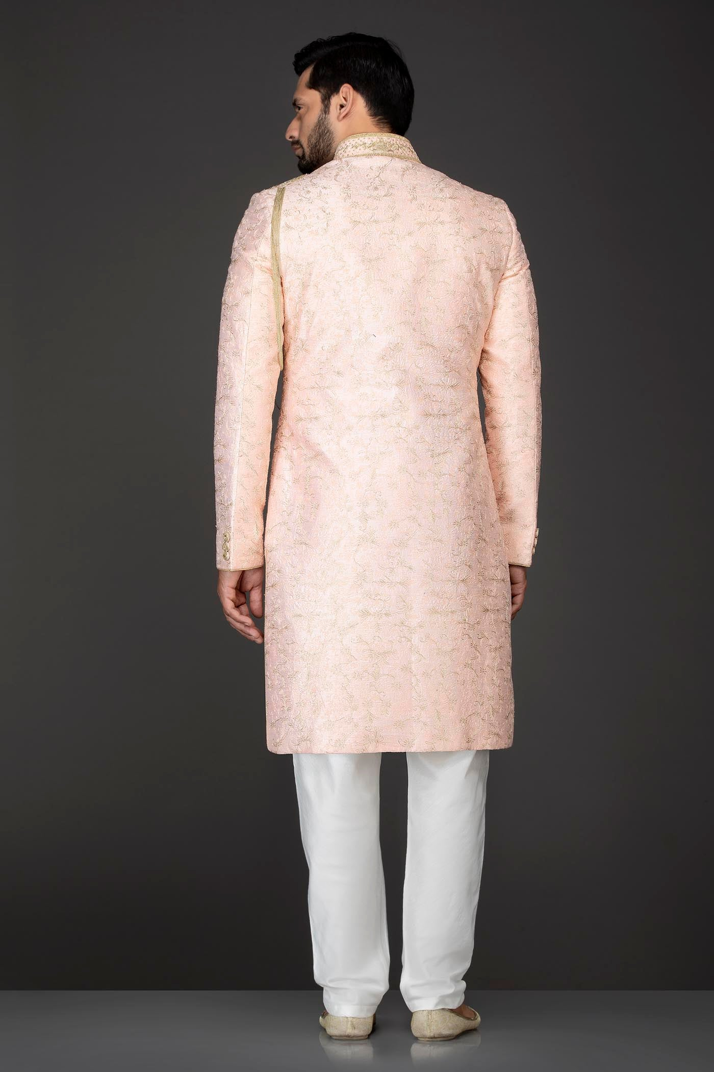 Peach Silk Sherwani With Embroidery On The Collar And Shoulder Brooch With Hanging Tassels Paired With White Trousers