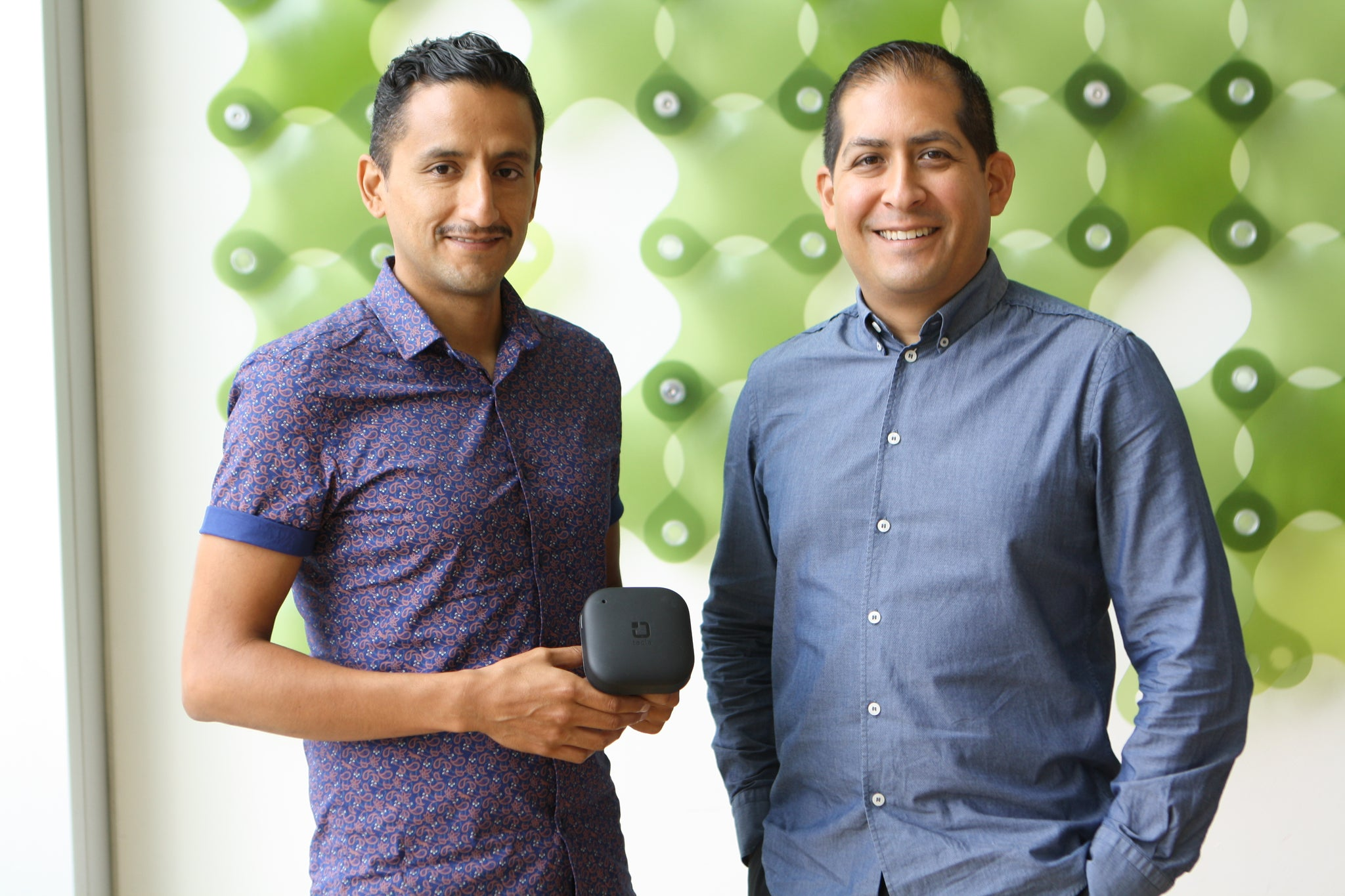 Jorge and Mauricio portrait shot standing in front of green background