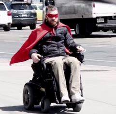 Ramp Man image - red cape blowing in the wind behind his wheelchair.