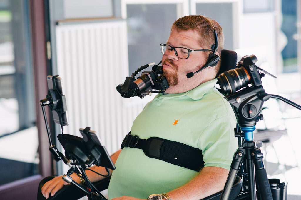 Man in wheelchair using sip-and-puff assistive switch