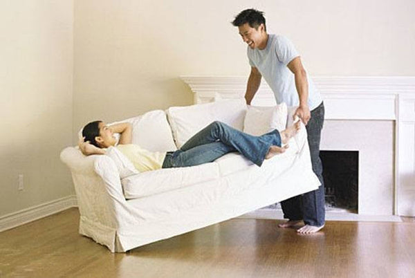 Image of man moving a couch with a woman sitting on it.