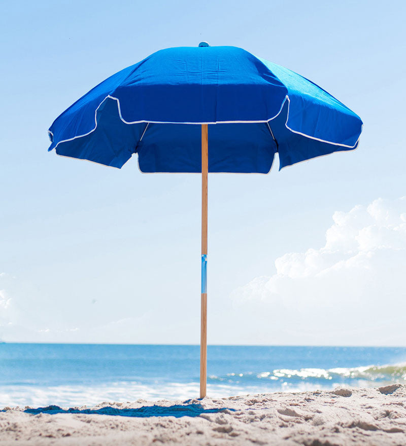 65 ft sunbrella beach umbrella with wood poles at beach