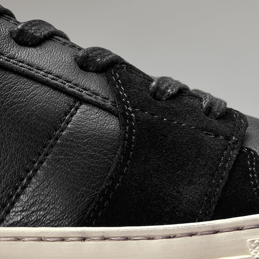 Detailed view of the side of the Men's Court Sneaker in Nero Black upper /  cream sole
