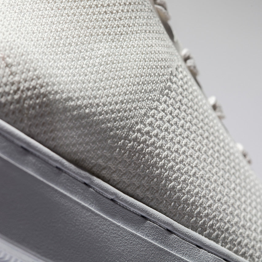 Detailed view of the side panel on the Men's Royale Knit Sneaker in Blanco White upper / Cadet Navy heel tab / white sole