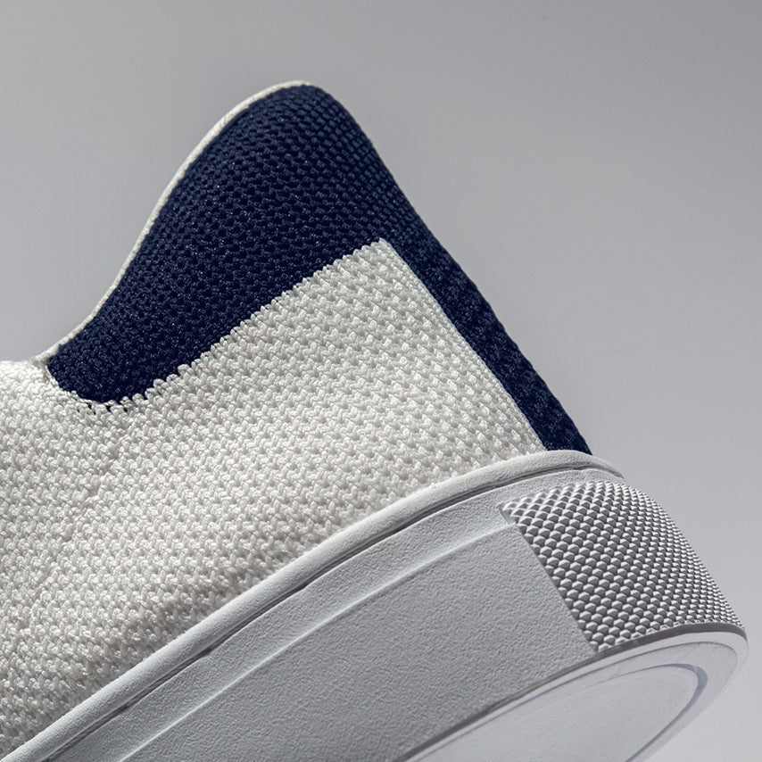 Detailed view of the heel of the Men's Royale Knit Sneaker in Blanco White upper / Cadet Navy heel tab / white sole.