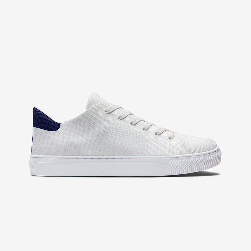 Profile view of the Men's Royale Knit Sneaker in Blanco white upper / Cadet Navy heel tab / white sole.