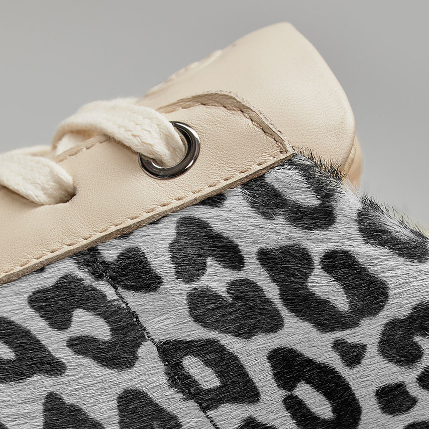 Detailed view of the eyelet and side panel of the Women's Royale Sneaker in Snow Leopard.