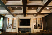 Antiqued Finished Entertainment Center with Floor To Ceiling Recess Panel Wainscot. Coffered Ceiling with Recess Lighting