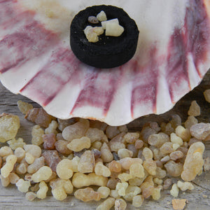 Photograph of frankincense resin with a charcoal briquet burning in a large shell