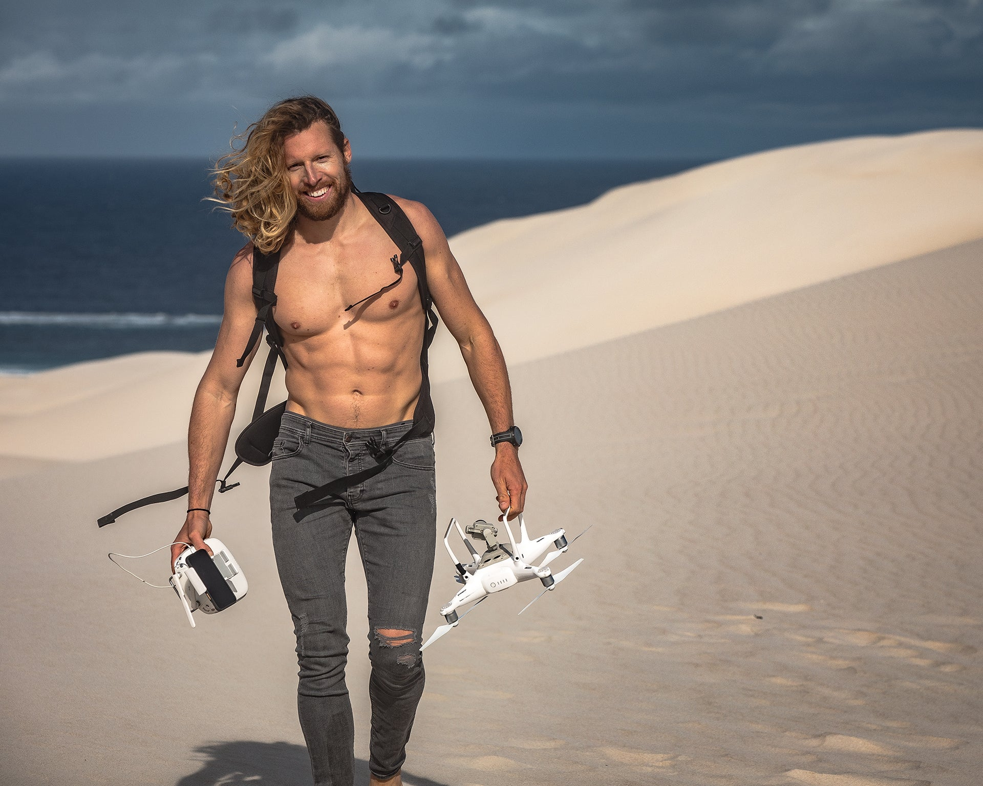 Phil Thurston walking through the desert with a DJI drone collecting photographs