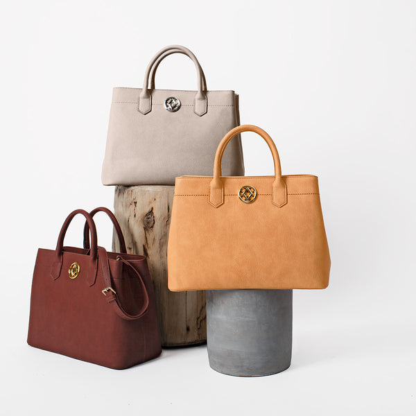 lovve cassy classic totes are shown on two pedestals in front of a grey background