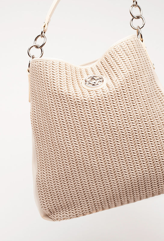 the lovve wendy woven bag hangs at a diagonal slant in front of a grey background